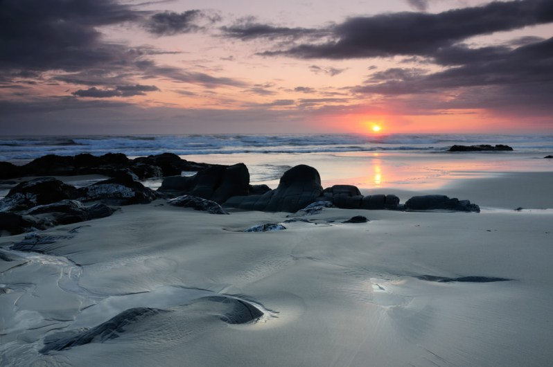 A sandy beach with smooth dark rocks, with the sun setting above the waves, under a pink sky and dark clouds