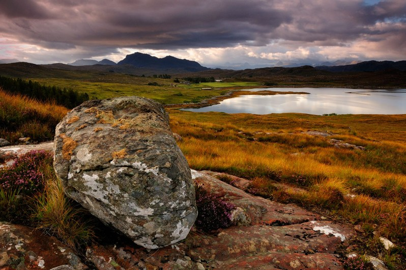 A grey boulder resting on pink rock in a landscape of green and rust coloured grass with mountains and a loch in the distance