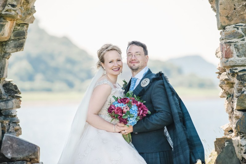 A bride and groom standing side by side in a stone archway holding flowers with water and hills in the background