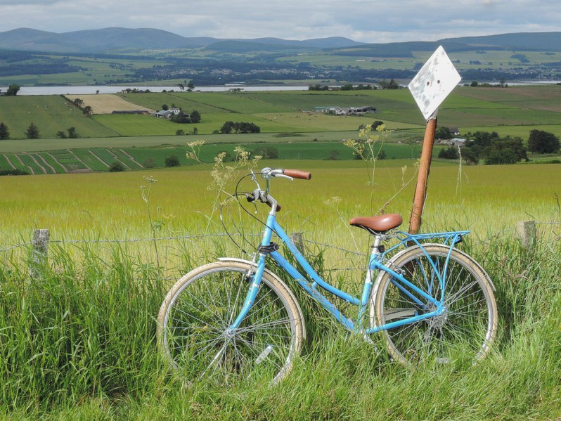 A traditional blue woman's bike leaning against a passing place sign in front of green fields with hills beyond