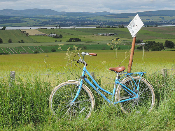 A blue Pendleton Somerby traditional bike propped up against a street sign in front of green fields with hills beyond