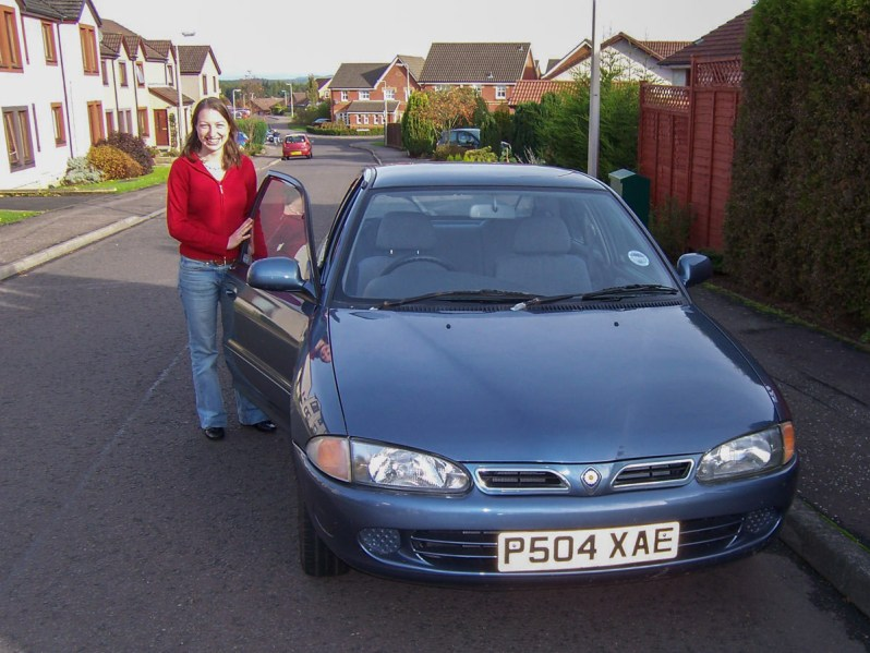 A young woman standing beside the open driver's door of a light blue Proton Persona car parked on a suburban street