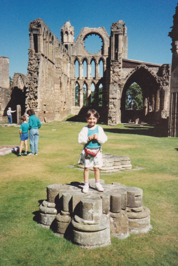 A young girl standing on a small stone pillar inside a large ruined cathedral with grass on the ground