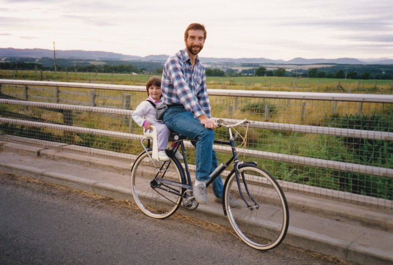 A young father on an old-fashioned bike with his small daughter seated on the back, with fields and hills in the background