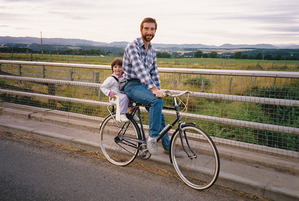 A young man on a traditional bike with his young daughter seated on the back, on a country road with fields and hills beyond