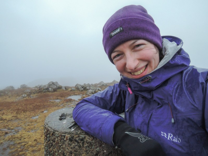 A woman wearing a purple jacket and hat, leaning on a stone pillar on top of a mountain, in wet and cloudy conditions