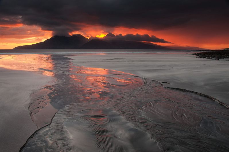 A dramatic red and yellow sunset over a mountainous island, with a sandy beach and a stream in the foreground