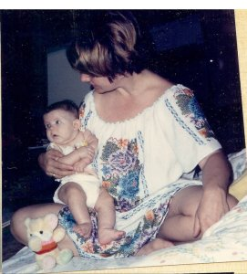 A young woman with short ash-blonde hair holds an infant with dark hair. The young woman's face is pointed away from the camera; she sits cross-legged and is dressed in a white dress covered in colorful embroidery.