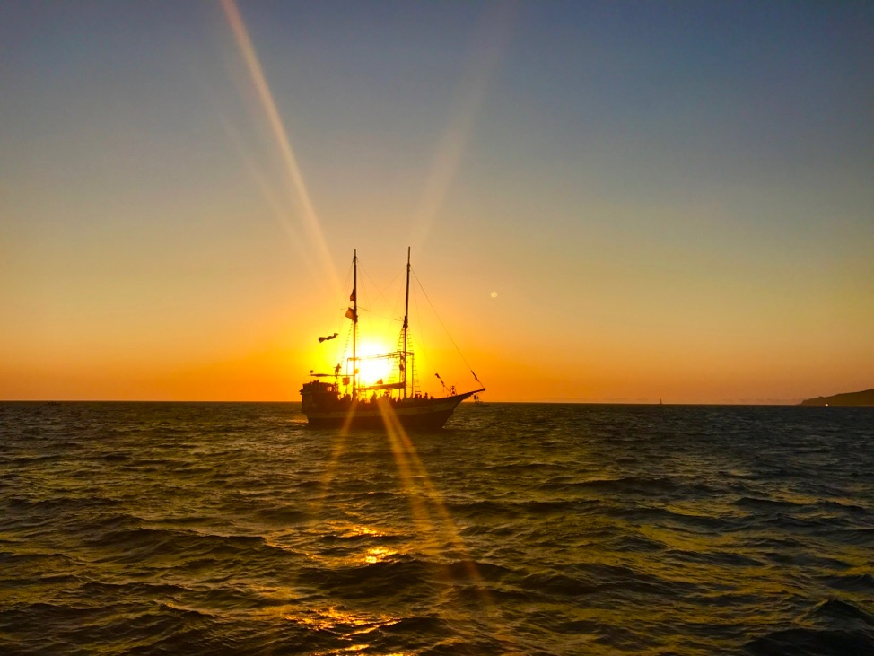 A pirate ship boat cruise sailing into the sunset.
