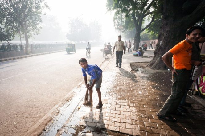 Boy cleaning the street in India
