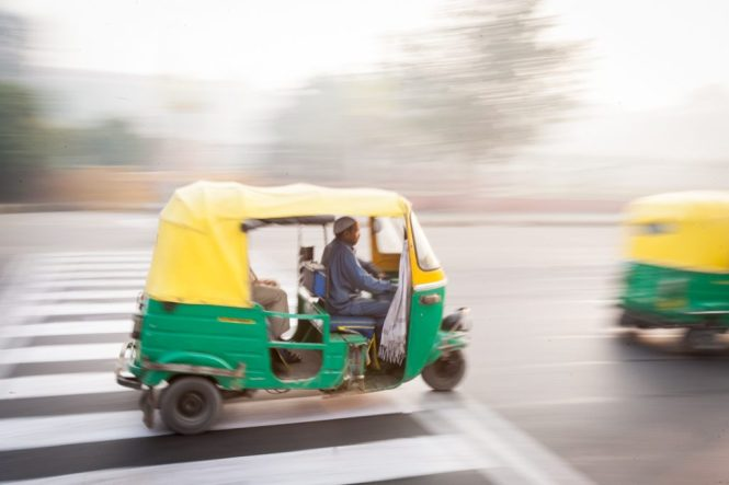 Tuk tuk speeding down the street in Delhi, India