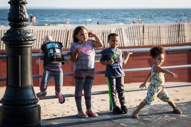 Coney Island street photography of kids posing for a photo on the boardwalk