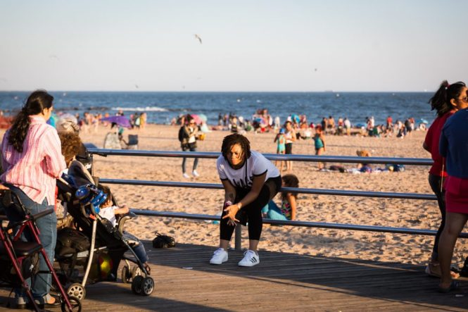 Coney Island street photography of a woman sitting on the boardwalk railing