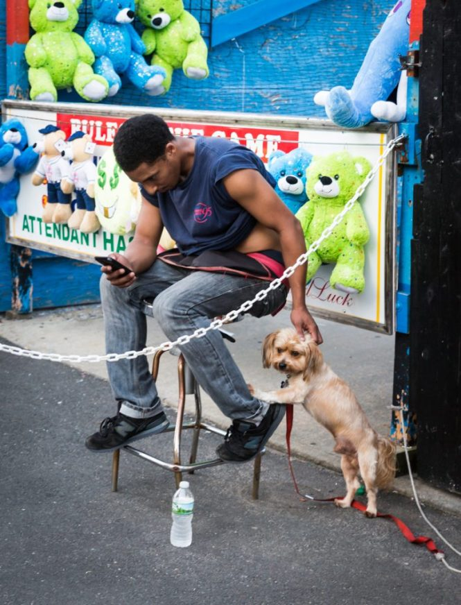 Coney Island street photography of a carnival worker petting dog