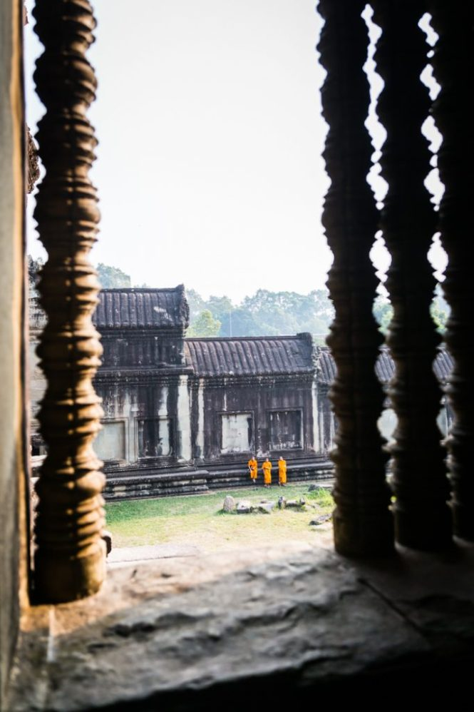 Monks through a window for an Angkor Wat temple guide