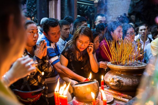 Woman lighting incense with cell phone at the Ba Thien Hau temple for article on Ho Chi Minh City street photos