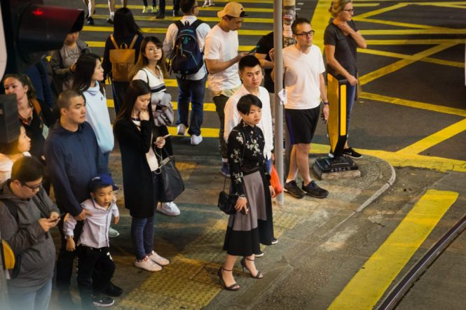 People waiting to cross the street for a Hong Kong street photography series called the view from the ding ding