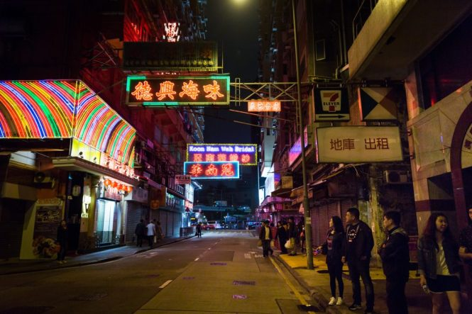 People looking at neon signs for a Hong Kong travel guide article