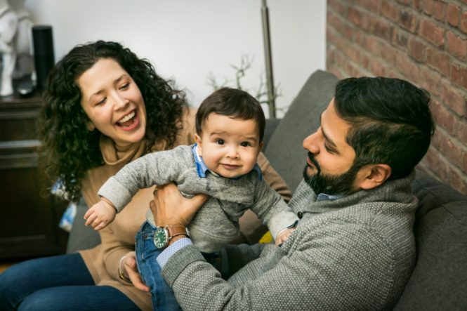 Parents playing with child for an article on indoor baby portrait tips