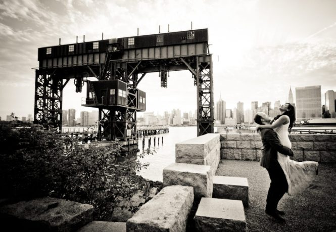Man lifting up woman at Gantry Plaza State Park for an article on best engagement photos