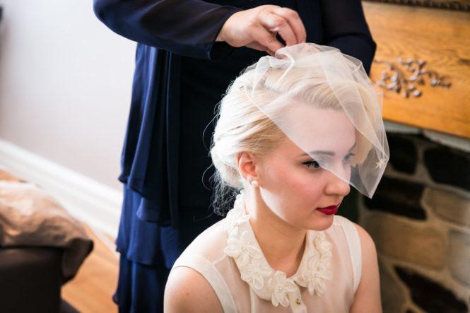 Bride putting on veil before her Scottadito wedding