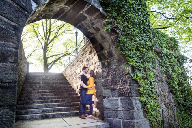 Kissing couple under arch at a Fort Tryon Park engagement portrait