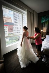 Bride getting into dress before a Brooklyn Historical Society wedding