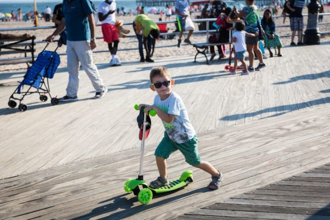 Kid on razor scooter on the Coney Island boardwalk