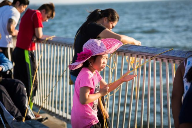 Girl in pink fishing on the Coney Island pier