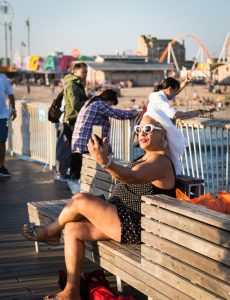 Woman with white turban talking into her phone on the Coney Island pier
