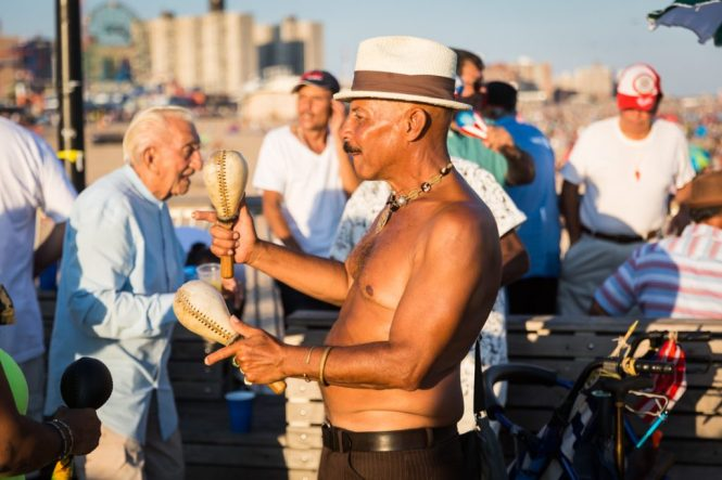 Shirtless man playing maracas on the Coney Island pier