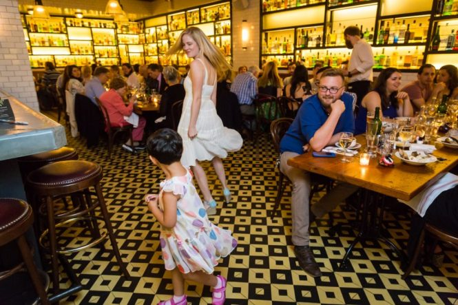 Little girl and bride at a rehearsal dinner for an article on details your wedding photographer needs to know