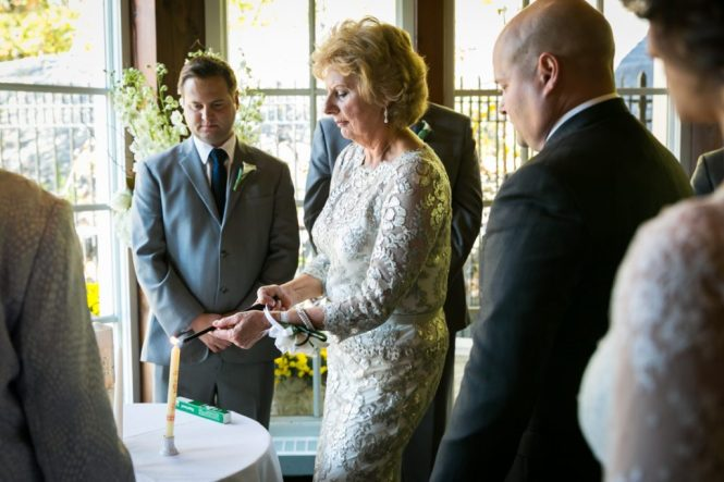 Mother of groom lighting a candle for an article on wedding officiant tips