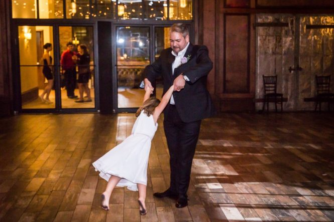 Groom and flower girl dancing at a 26 Bridge wedding