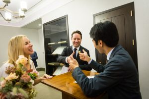 Bride, groom, and wedding officiant for an article on How to Get Married at City Hall in Any NYC Borough