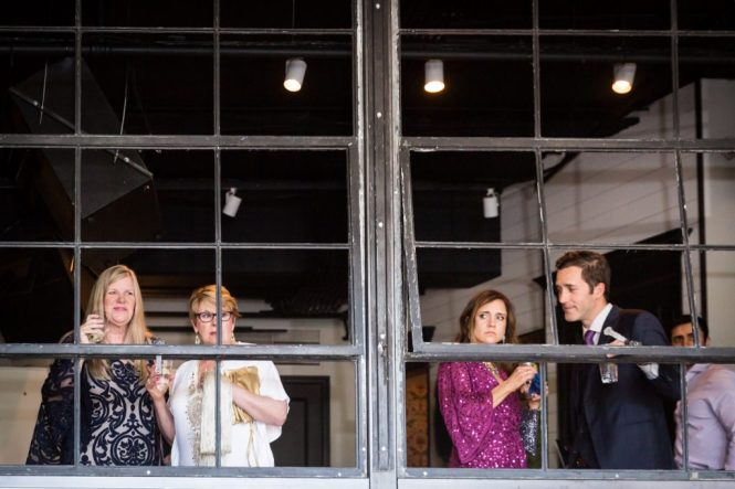 Guests looking through window at a same sex wedding celebration in Washington DC