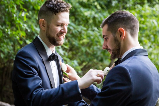 Grooms adjusting each others boutonnieres for an article entitled, 'Do you need a permit to get married in Central Park?'