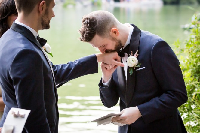 Groom kissing groom's hand for an article entitled, 'Do you need a permit to get married in Central Park?'