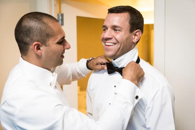 Groom adjusting groomsman's tie for an article on Bronx Zoo wedding venue updates