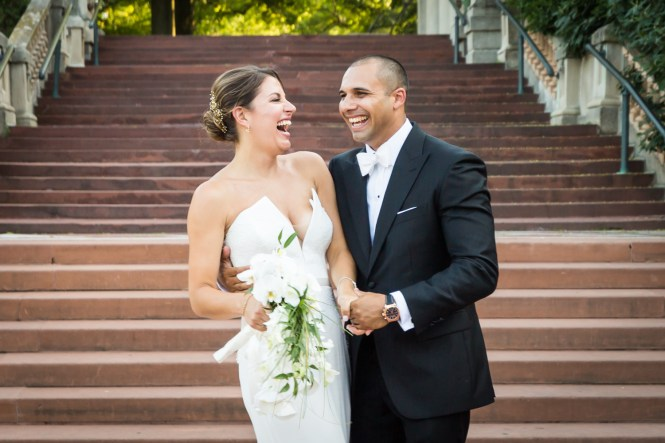 Bride and groom on Bronx Zoo entrance staircase for an article on Bronx Zoo wedding venue updates