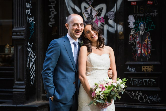 Portrait of bride and groom against graffiti for an article on non-floral centerpiece ideas