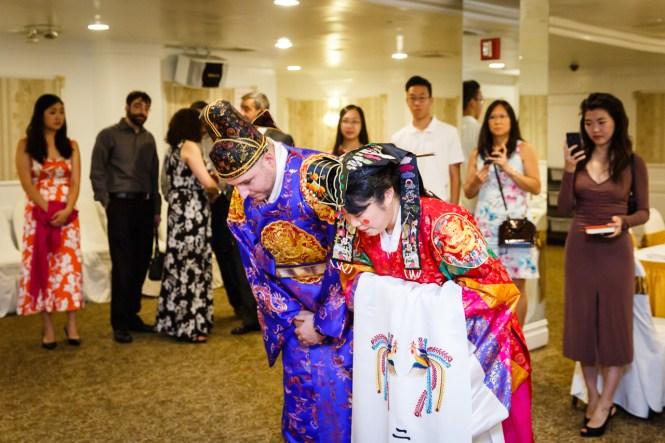 Bride and groom bowing at traditional Korean pyebaek ceremony