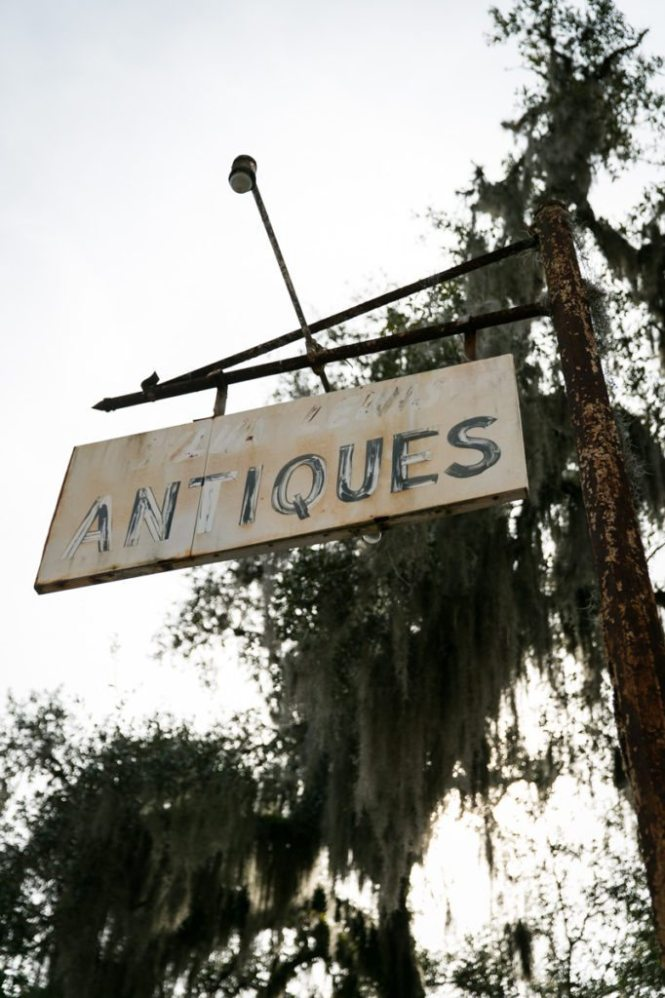 A faded sign for an antiques store