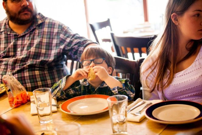 A kid eating, by NYC bat mitzvah photographer, Kelly Williams