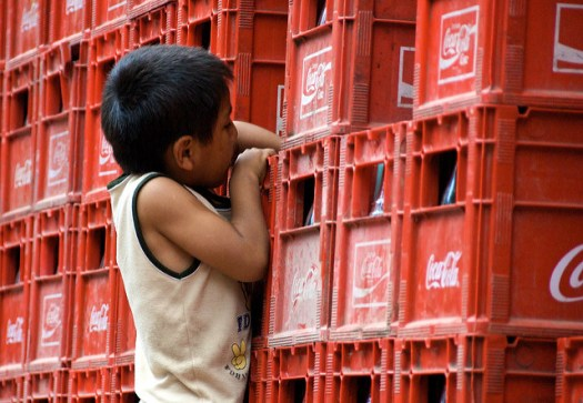 A picture of a young boy stretching out his arm across a crate of Coca Cola to reach a bottle.