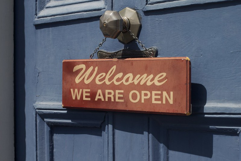 "A sign hanging from a door know stating ""Welcome, We are Open"""