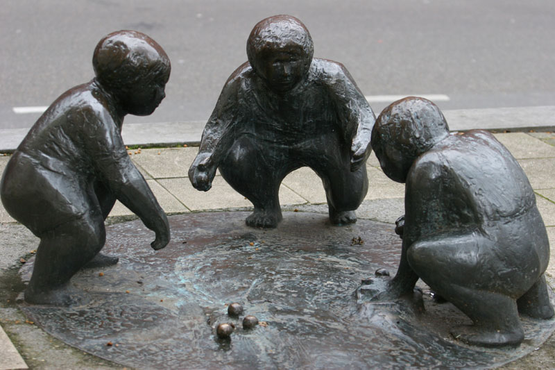 What appears tobe a small sculpture of 3 children playing marbles.