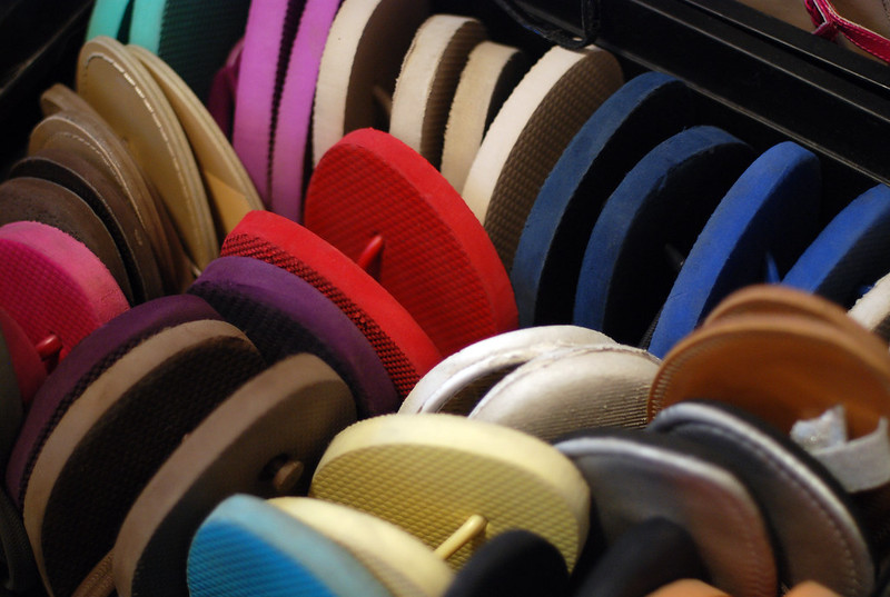 Collection of various coloured flip flop sandals upright in a drawer.