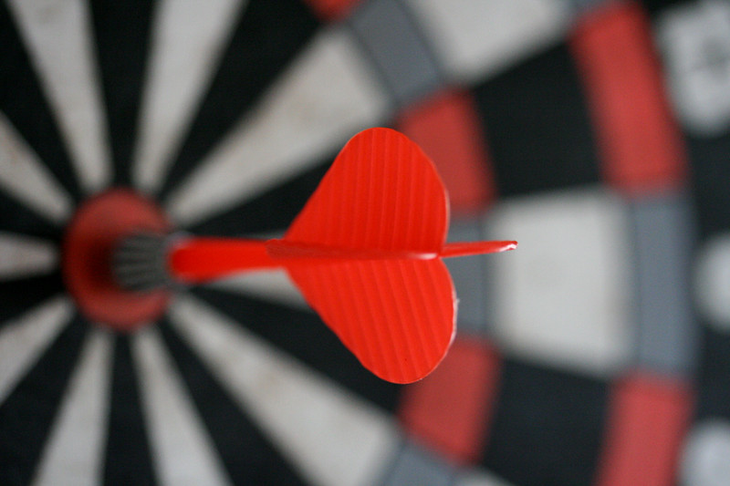 Close up of a red dart hitting a bullseye in darts.