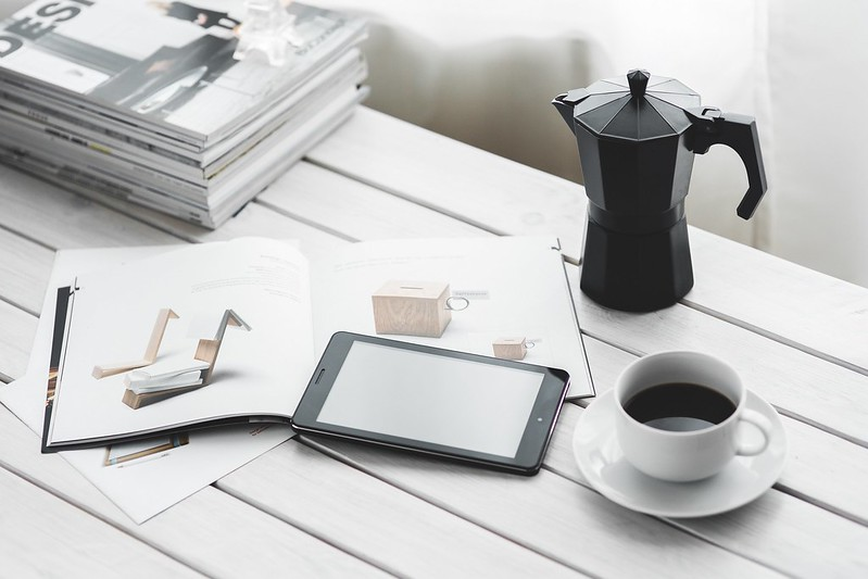 Picture with coffee, kindle reader, moka pot , a book and magazines on a table.